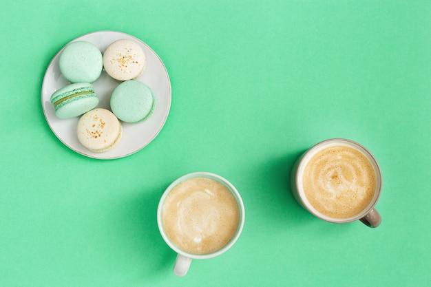 Zwei tasse kaffee cappuccino und süße dessertmakronen in weißer platte auf minzpapier. morgenkaffeetassenkonzept. draufsicht. flach liegen.