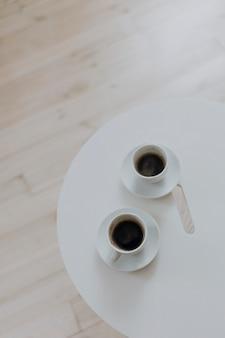 Zwei tasse kaffees auf einer weißen tabelle