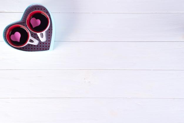 Zwei tasse kaffees in einer kastenform eines herzens auf einem weißen hintergrund. valentinstag