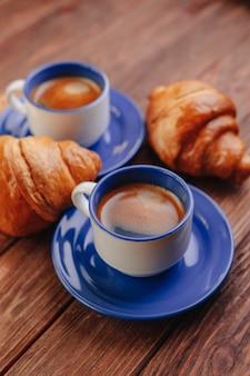 Zwei tasse kaffees und hörnchen auf einem hölzernen hintergrund, gutes licht, morgenatmosphäre