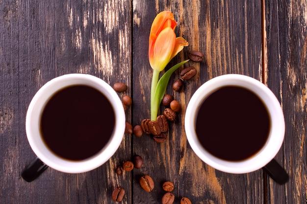 Zwei tasse kaffees und kaffeebohnen auf dunklem hölzernem hintergrund.