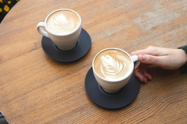 Zwei tassen cappuccino auf einem holztisch mit den händen