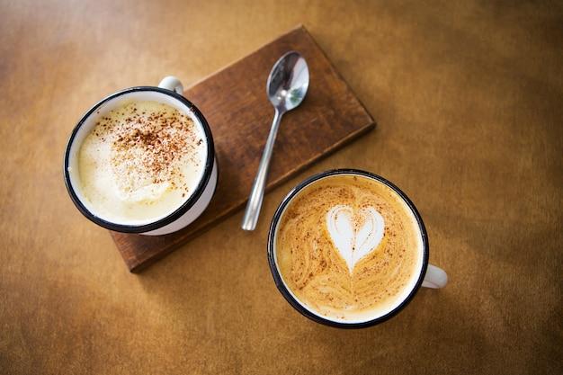 Zwei tassen cappuccino und latte stehen auf einem holztisch