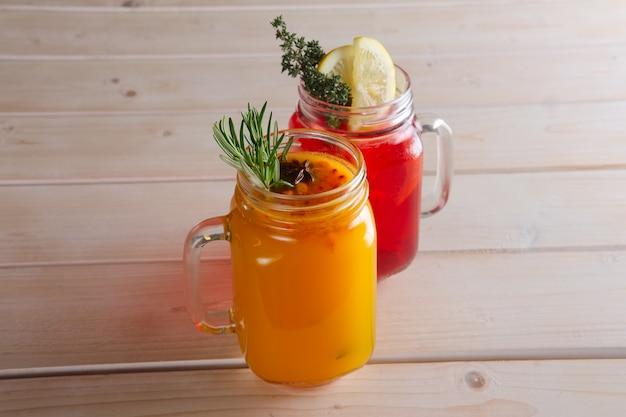 Zwei tassen cranberry-tee und sanddorn-tee mit zitrusfrüchten, zimt und rosmarin
