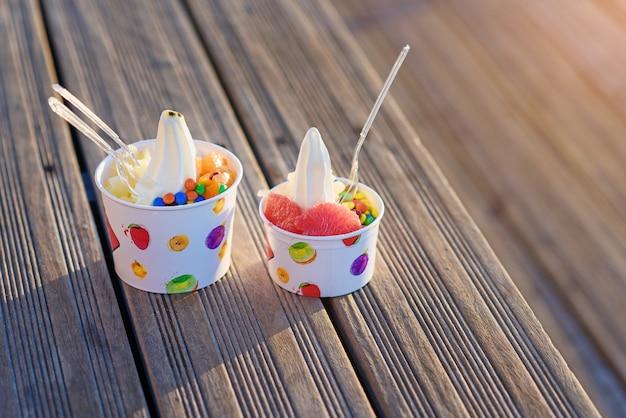 Zwei tassen eis mit süßigkeiten auf sonnenuntergang.