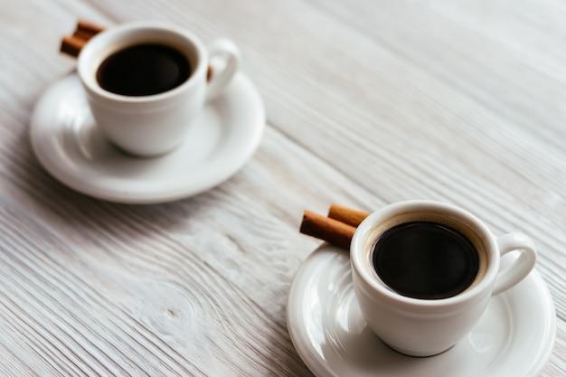 Zwei tassen espresso mit zimtstangen auf einem weißen holztisch