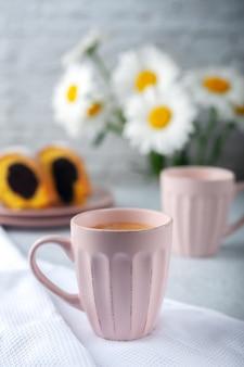 Zwei tassen frisch zubereiteten kaffee mit sahne mit cupcake und kamillenblüten