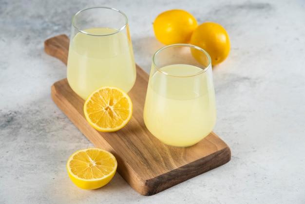Zwei tassen frische limonade auf einem holzbrett.