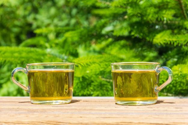 Zwei tassen grüner tee auf dem tisch im freien an einem sonnigen sommertag, auf einem natürlichen grün