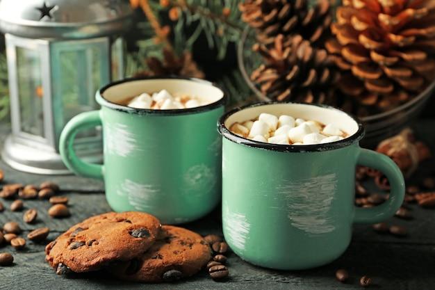 Zwei tassen heißen kakao mit marshmallow und keksen auf schwarzem tisch