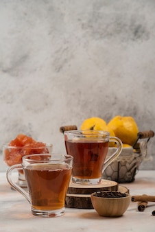Zwei tassen heißen tee mit marmelade auf marmortisch.