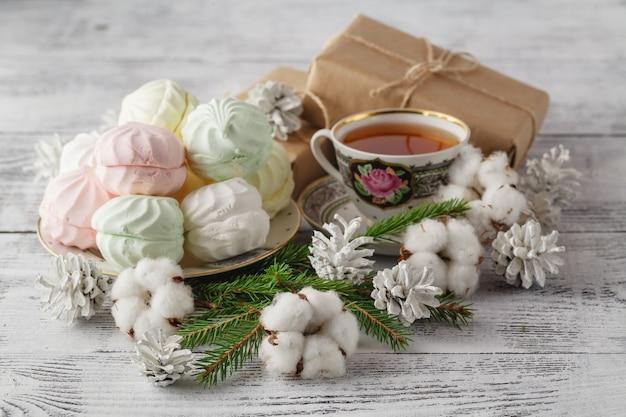 Zwei tassen heißen tee und baumwollblumen auf rustikaler betonoberfläche. weihnachts- oder valentinstagfeierkonzept.