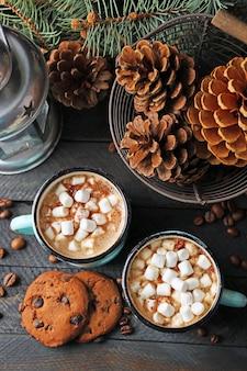 Zwei tassen heißer kakao mit marshmallow und keksen auf schwarzem tisch