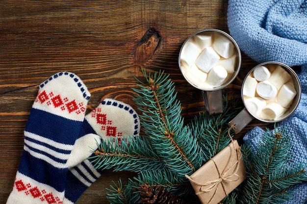 Zwei tassen heißer kakao oder schokolade mit marshmallow-fäustlingen weihnachtsdekor und tannenbaum auf holzr...