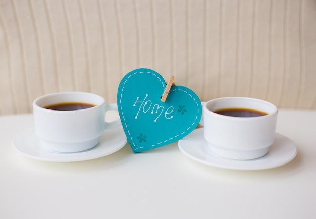 Zwei tassen kaffee auf dem tisch und ein herz