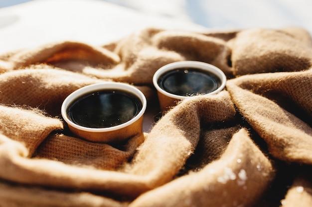 Zwei tassen kaffee auf einem schal im verschneiten wald.