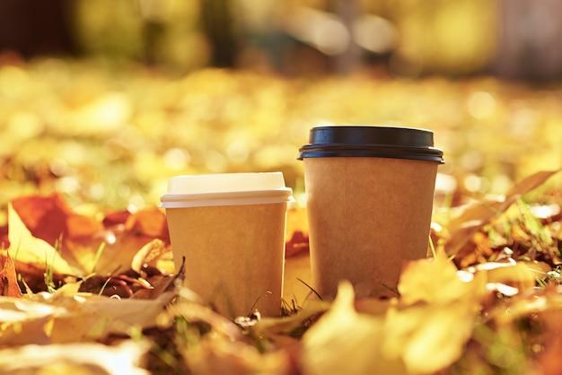 Zwei tassen kaffee auf herbstgoldenen blättern