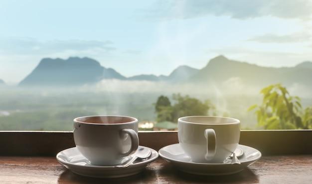 Zwei tassen kaffee auf holztisch am morgen mit sonnenlicht über verschwommener berglandschaft