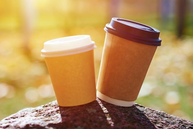 Zwei tassen kaffee im herbstpark, nahaufnahme