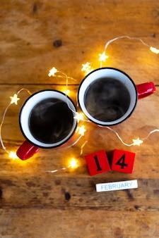 Zwei tassen kaffee in roten tassen an einer wand aus girlanden. morgenfrühstück zum valentinstag. von oben betrachten.