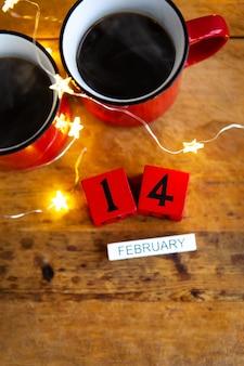 Zwei tassen kaffee in roten tassen auf dem tisch mit lichtern. morgenfrühstück zum valentinstag. von oben betrachten.