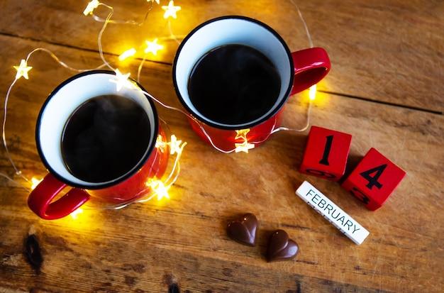Zwei tassen kaffee in roten tassen auf einem tisch mit schokoladenherzen. valentinstag morgen überraschung.