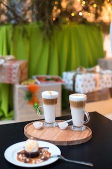 Zwei tassen kaffee latte und kuchen auf weihnachtsbaum und geschenke