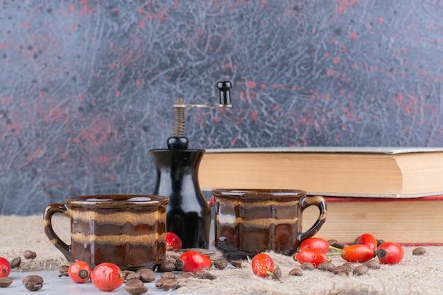 Zwei tassen kaffee mit bohnen und hagebutten auf dem tisch. foto in hoher qualität