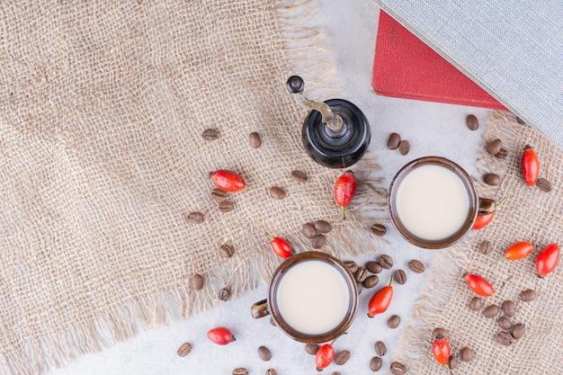 Zwei tassen kaffee mit bohnen und hagebutten auf sackleinen.