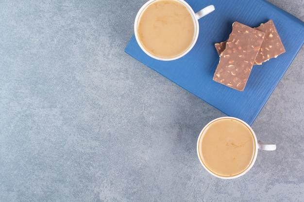 Zwei tassen kaffee mit pralinen auf buch.