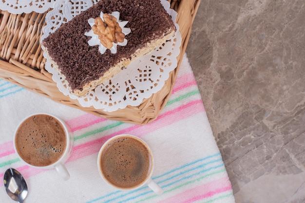 Zwei tassen kaffee mit süßem kuchen auf marmortisch