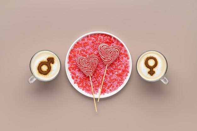 Zwei tassen kaffee mit symbolen des mannes und der frau auf geschlagenem milchschaum und lutschern in herzform auf weißem teller. beiger hintergrund. konzept romantisches datum am valentinstag. flach liegen