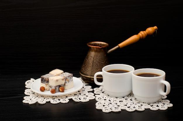Zwei tassen kaffee, türkisches lokum mit haselnuss, cezve