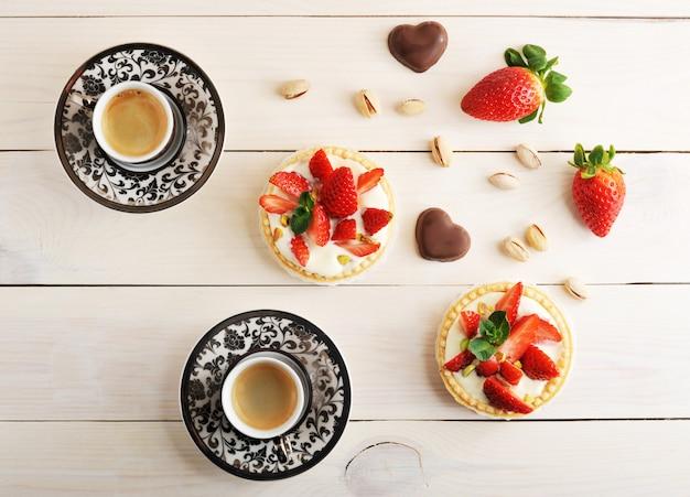 Zwei tassen kaffee und ein gebäckkorb mit erdbeere, pistazie, buttercreme