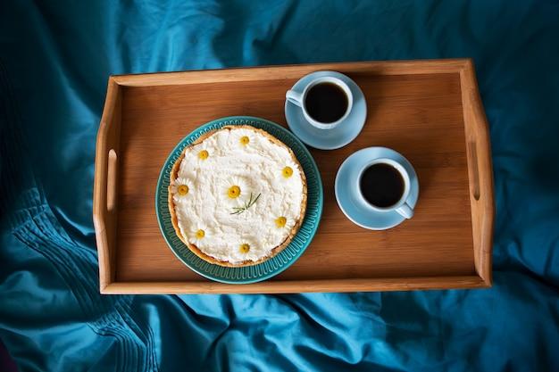 Zwei tassen kaffee und käsekuchen stehen auf einem holztablett, draufsicht.