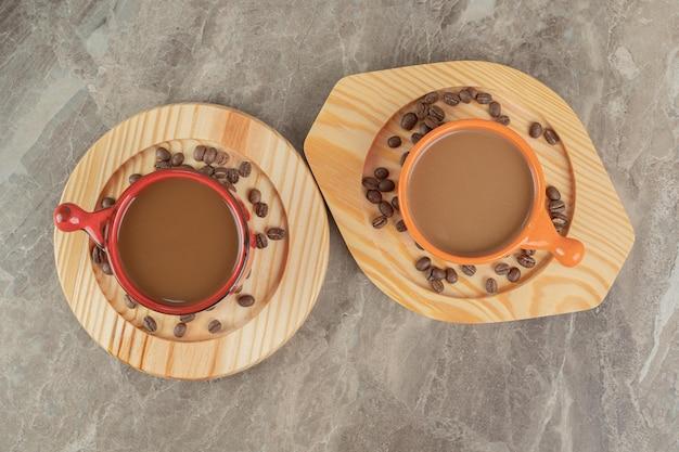 Zwei tassen kaffee und kaffeebohnen auf holztellern