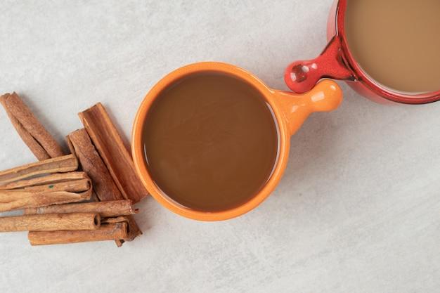 Zwei tassen kaffee und zimtstangen auf marmoroberfläche