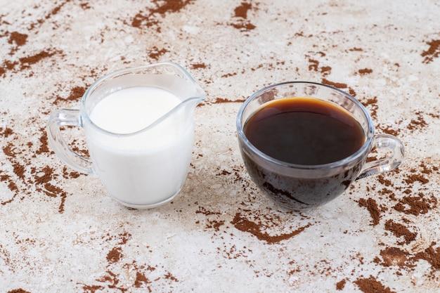 Zwei tassen milch und tee auf einer marmoroberfläche