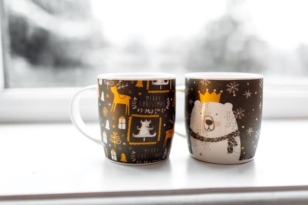 Zwei tassen mit einem heißen getränk, weihnachtsdekor, beleuchtungen auf einer fensterbank mit winterhintergrund, konzept der familienwinterferien.