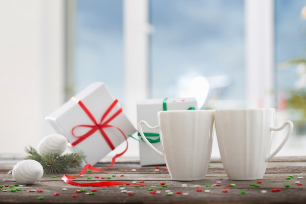 Zwei tassen mit geschenken auf hintergrundweihnachtsbaum