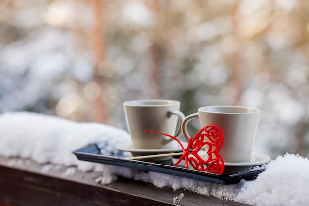 Zwei tassen mit heißem kaffee oder tee zusammen mit herzen