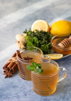 Zwei tassen mit heißem tee mit kräutern, gewürzen, zitrone, ingwerwurzel und honig. kräutertee mit minze und thymian.