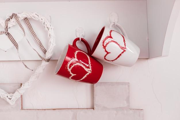 Zwei tassen mit herzen in der küche und einem hölzernen weißen herzen. valentinstag zusammensetzung