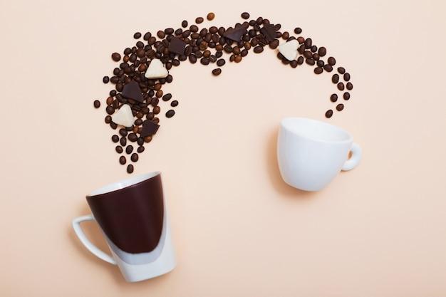 Zwei tassen mit kaffeebohnen auf hellem hintergrund