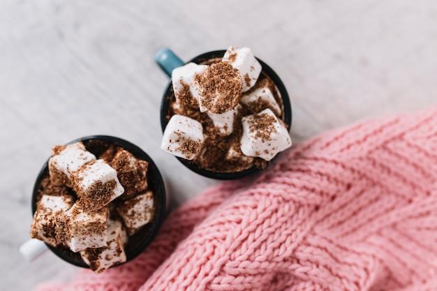 Zwei tassen mit marshmallows und gestricktem schal