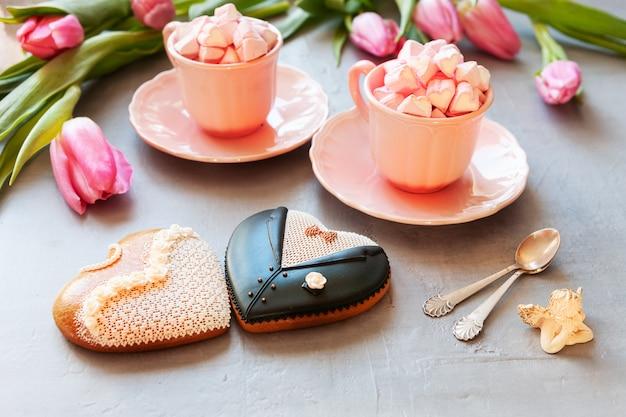 Zwei tassen mit rosa tulpen und zwei lebkuchenbraut