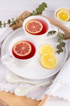 Zwei tassen rote frucht und kräutertee mit zitronenscheibe, draufsicht