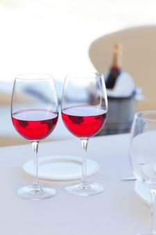 Zwei tassen rotwein und flasche in eiskübel