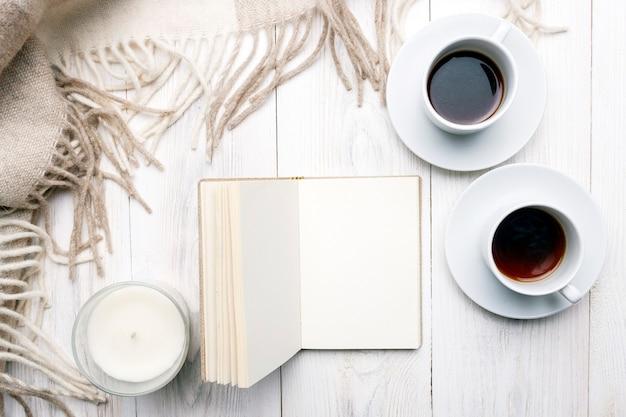 Zwei tassen schwarze kaffeekerze offenes notizbuch beige wollplaid