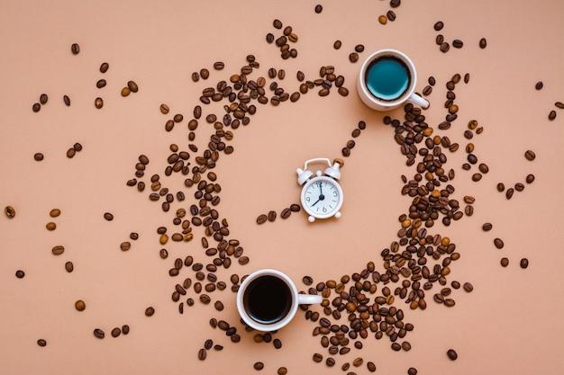 Zwei tassen schwarzer kaffee im kreis aus kaffeebohnen und ein weißer wecker auf beigem hintergrund. zeit, kaffeekonzept zu trinken. ansicht von oben